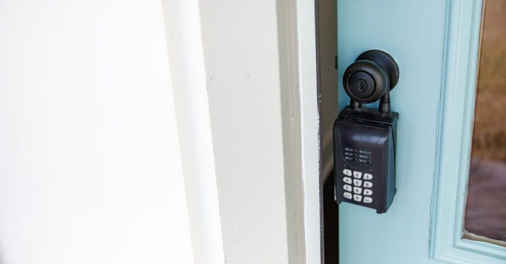 A black electronic lockbox hanging from a bronze doorknob
