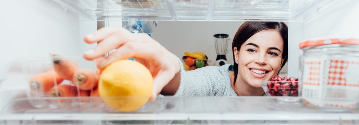 Smiling woman taking a fresh lemon out of the fridge, healthy food concept